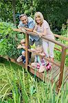 Grandparents and grandchildren smiling on wooden footbridge