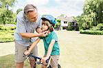 Grandfather adjusting bicycle helmet on grandson