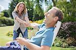 Woman pulling boyfriend out of chair in backyard