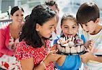 Children holding birthday cake outdoors