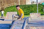 smiling teenage boy in roller-blading protection kit in a skate park