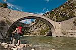 Female hiker looking towards bridge, Canyon du Verdon, Provence, France
