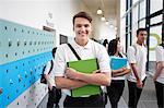 Portrait of teenage boy holding file in school corridor
