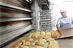 Baker putting bread onto baking sheet