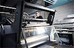 Worker operating printing machine in print workshop