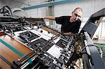 Worker monitoring print machine in printing workshop