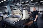 Worker operating print machine in printing workshop
