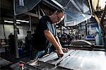 Worker servicing print machine in printing workshop