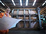Engineer inspecting engineering drawings in factory