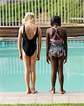 Two multi-racial girls standing on edge of pool. Windhoek, Namibia.