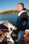 Smiling man with dog on boat, Ronneby, Blekinge, Sweden