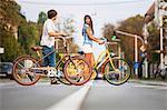 Young couple pushing bicycles together, Osijek, Croatia
