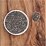 Chia seed healthy super food over olive wood background. Salvia hispanica.