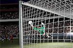 Goalie defending soccer net on field