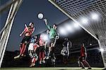 Soccer players defending goal