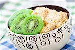Bowl of oats porridge with kiwi on a table