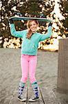 Teen balances skateboard on her head