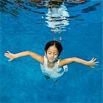 Girl (5 years) swimming underwater in white dress.