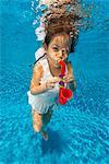 Child (5 years) playing toy saxophone underwater.