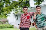Two boys in a farmhouse garden in summer.