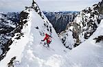 A skier ski-ing down The Slot snow slope on Snoqualmie Peak in the Cascades range, Washington state, USA.