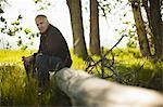 A man sitting on a fallen tree trunk in woodland.