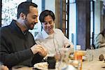 Men sharing text at restaurant table