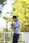 Father bottle feeding son outdoors