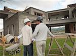 Architects  holding   blueprints outside house under construction