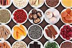Healthy super food selection in porcelain bowls over brown lokta paper background.