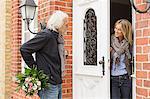 Senior man with bouquet, mid adult woman opening front door