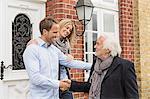 Mid adult couple by front door, senior man shaking hands