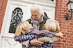 Grandfather hugging grandchildren by front door