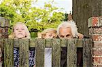 Grandfather and grandchildren peering over wooden gate