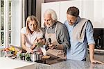 Senior man with mid adult couple preparing food