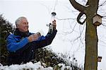 Senior man filling bird feeders in garden in winter