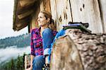 Woman enjoying the view from wooden shack, Tirol, Austria
