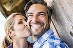 Woman kissing man's cheek outside wooden shack