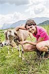 Young woman feeding goat, Tyrol, Austria