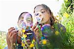 Sisters sitting in field of flower blowing bubbles