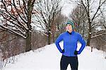 Female jogger taking a break in snow covered scene
