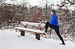 Female runner doing stretch exercises in snow