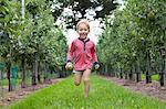 Boy running through apple orchard