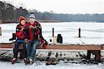 Couple sitting on pier having hot drink