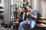 Couple using digital tablet together on sidewalk bench