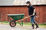 Side view of female farmer pushing wheelbarrow on rural road