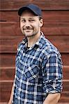 Portrait of confident farmer smiling against barn