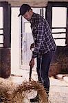 Full length of farmer shoveling hay in barn