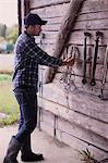 Full length of farmer arranging rope in barn