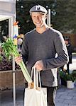 Portrait of happy man holding celery in market